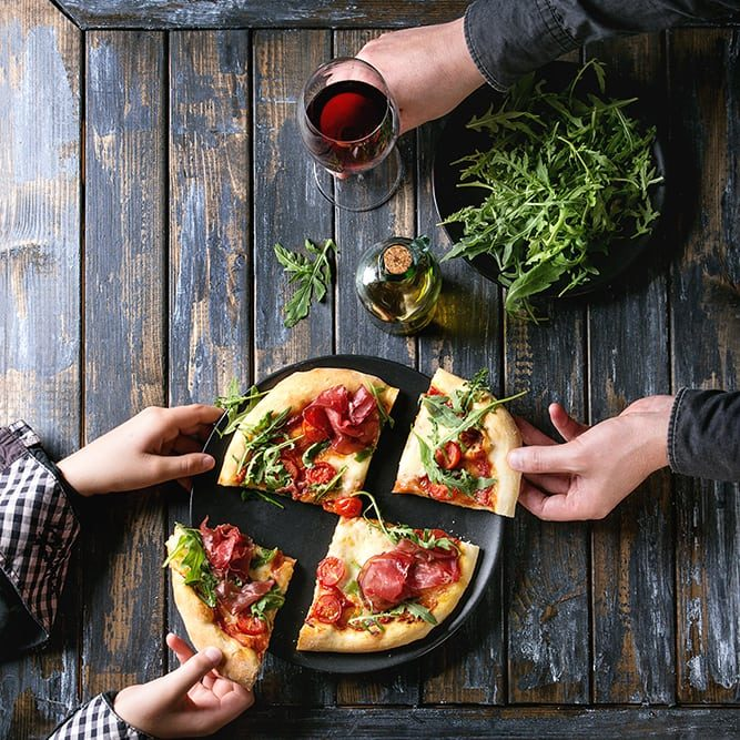 Hands taking sliced homemade pizza with cheese and bresaola, served on black plate with fresh arugula, olive oil, glass of red wine and kitchen towel over old wooden plank background. Flat lay.